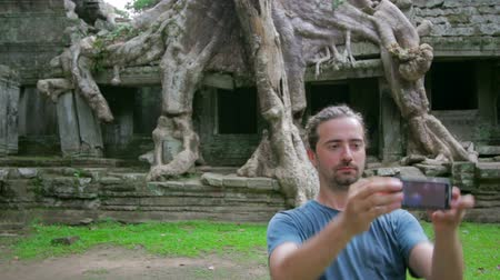 руины : visitor taking picture bizarre nature of preah khan temple, angkor Стоковые видеозаписи