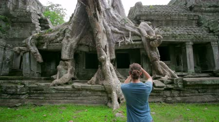 tek başına : visitor taking picture bizarre nature of preah khan temple, angkor Stok Video