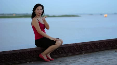 sending : chinese business woman listening music sent kisses at riverside