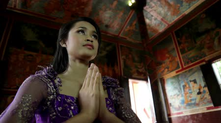 délkelet Ázsia : Asian girl praying in temple, wat, pagoda, Phnom Penh, Cambodia