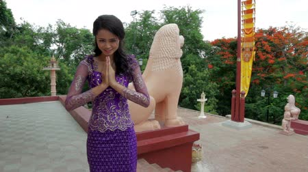 sayesinde : Asian Girl Greets in temple traditional way with both hands Stok Video
