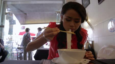 нездоровое питание : Asian girl eating noodle in a local restaurant, phnom penh Стоковые видеозаписи