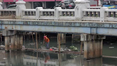 feiúra : indonesian man working in unhealthy open sewer of jakarta