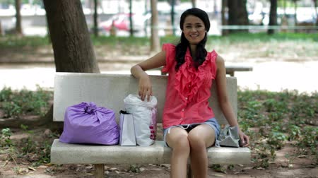único : Asian girl resting on bank bench after carrying shopping bags Vídeos