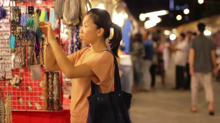 bugiganga : Chinese Young Woman Shopping at asian night market Stock Footage