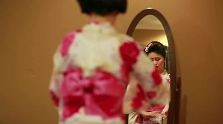 Японская культура : Japanese geisha making up on mirror on orange background
