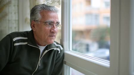 looking : Senior man wearing tank suit and glasses looking through window Stock Footage