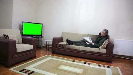 sitting room : Senior man watching TV show while sitting on sofa in his living room