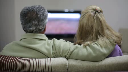 televízió : Senior couple sitting together on sofa, watching television