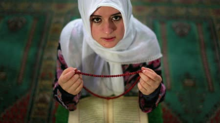 modlitba : Muslim girl saying her everyday salat prayer, using prayer beads