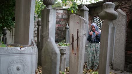 могила : Muslim girl praying in small graveyard