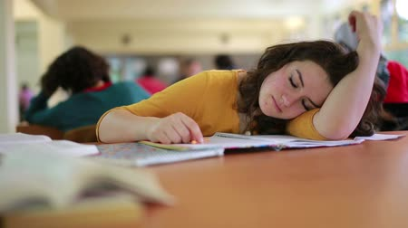 adormecido : Girl falling asleep over book in library reading room