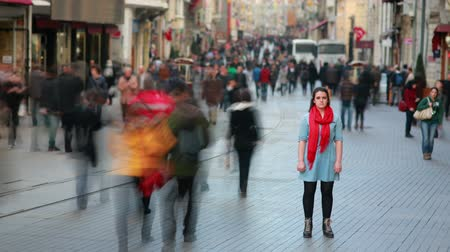 стоять : Young woman standing in busy city street, fast motion