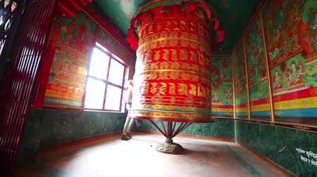 modlitba : Female walking around Prayer wheel in spin at the holy Buddhist site of Boudhanath, Kathmandu, Nepal