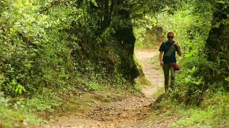 поход : Female Caucasian tourist trekking walking along narrow footpath at himalayan mountains, Nepal
