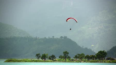 pára quedas : Paraglides in the sky over Pokhara Lake, Nepal