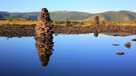 zen como : Zen like Religious stone structures on lakeshore at central mongolia. relax, easy going, meditative landscape with water reflection. stones on balance, symbol of balance of life. there is nobody. silence, simplicity peaceful background. buddhism religion
