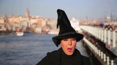 ведьма : Woman with witch hat outside istanbul city Стоковые видеозаписи