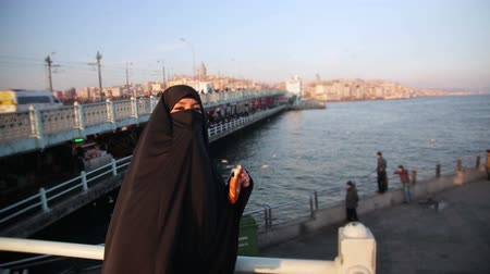 bécsi kifli : Woman dressed with black headscarf, chador eating simit, turkish bagel with istanbul city view, turkey Stock mozgókép