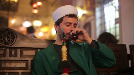 muslim leader : islamic man with traditional dress smoking shisha, drinking tea Stock Footage