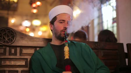 muslim leader : islamic man with traditional dress smoking shisha, istanbul, turkey