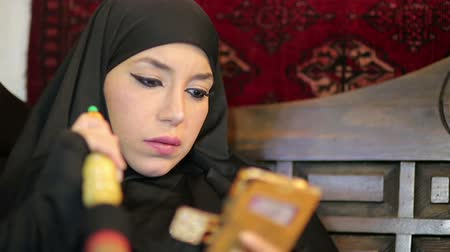 başörtüsü : Woman with chador headscarf smoking shisha and using mobile phone