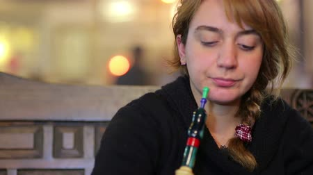 fumegante : secular turkish woman smoking shisha at nargile cafe shop