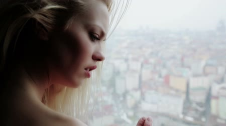 lonely : lonely woman looking through window to city view