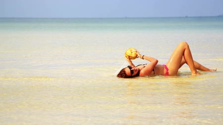areia : Woman sunbathing crystal water drinking coconut enjoying vacation, cambodia