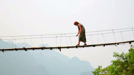 corda : Zoom, Pan, Tourist woman crossing dangerous bamboo bridge, limestone view, vang vieng, laos