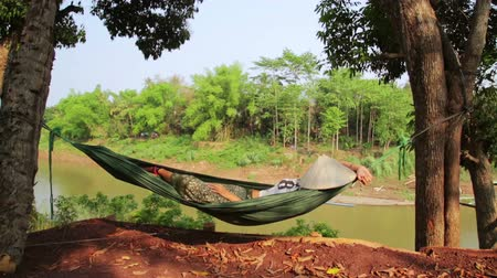 prabang : tourist girl sleeping on hammock, luang prabang, laos