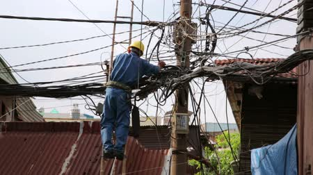 elektryk : electrician fixing, repairing messy electric cables in hanoi slums, vietnam