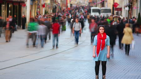 вокруг : Young woman posing, busy street, people walking around, HD, zoom in extra Стоковые видеозаписи