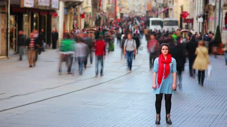 blur : Young woman posing, busy street, people walking around, 4K, zoom in