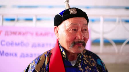 yarışma : ULAANBAATAR, MONGOLIA - JULY 2013: Mongolian man with traditional clothes posing during Naadam Festival Knucklebone Tournament Stok Video