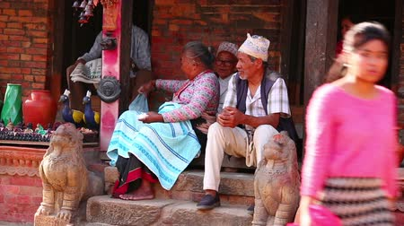 patan : KATHMANDU, NEPAL - JUNE 2013: everyday life at bhaktapur street, local people sitting outside