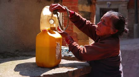 patan : KATHMANDU, NEPAL - JUNE 2013: old woman pulling water containers from well