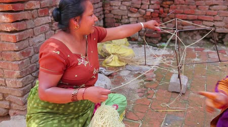 patan : KATHMANDU, NEPAL - JUNE 2013: local woman knitting at street Stock Footage