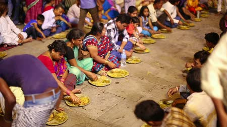 hacı : VARANASI, INDIA - MAY 2013: poor indian people eating free food at street at night