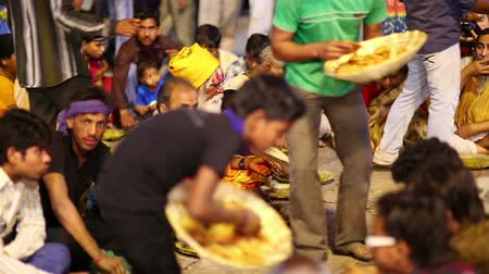 голодный : VARANASI, INDIA - MAY 2013: poor indian people eating free food at street at night