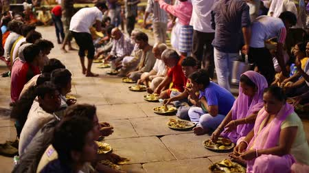 dobrovolník : VARANASI, INDIA - MAY 2013: poor indian people eating free food at street at night