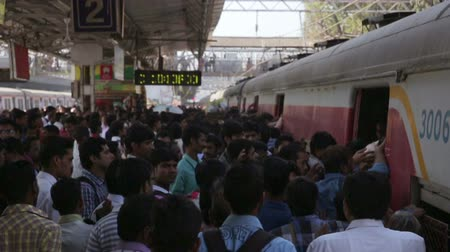бросаясь : MUMBAI, INDIA - MARCH 2013: People getting on overcrowded train during rush hour Стоковые видеозаписи