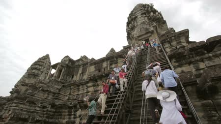 руины : ANGKOR WAT - JUNE 2012: tourists climbing steps of angkor wat Стоковые видеозаписи