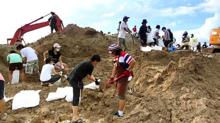 voluntário : Volunteers to stop the flood in Bangkok Thailand. Mainly Soldiers and students are making sandbags