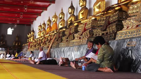 boudha : people sits under golden buddha statues
