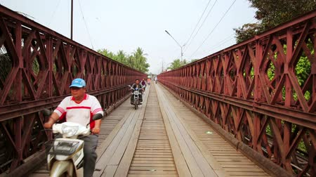 prabang : LUANG PRABANG, LAOS - APRIL 2014: motorbikes crossing historical iron bridge
