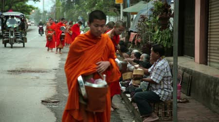 szerzetes : LUANG PRABANG, LAOS - APRIL 2014: people give rice to monks as gift and get their blessing in their everyday morning religious ceremony Stock mozgókép