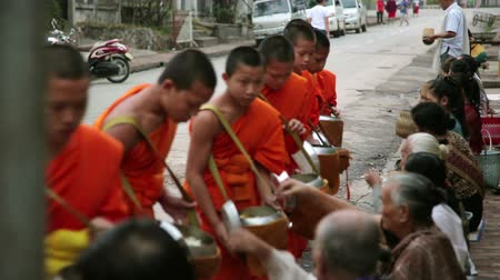 nimet : LUANG PRABANG, LAOS - APRIL 2014: people give rice to monks as gift and get their blessing in their everyday morning religious ceremony Stok Video