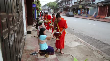 prabang : LUANG PRABANG, LAOS - APRIL 2014: people give rice to monks as gift and get their blessing in their everyday morning religious ceremony Stock Footage