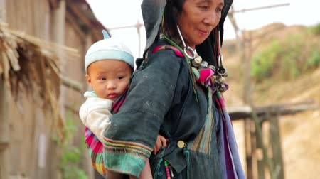 obec : PONGSALI, LAOS - APRIL 2014: indigenous tribal native Akha woman carry baby in hill village